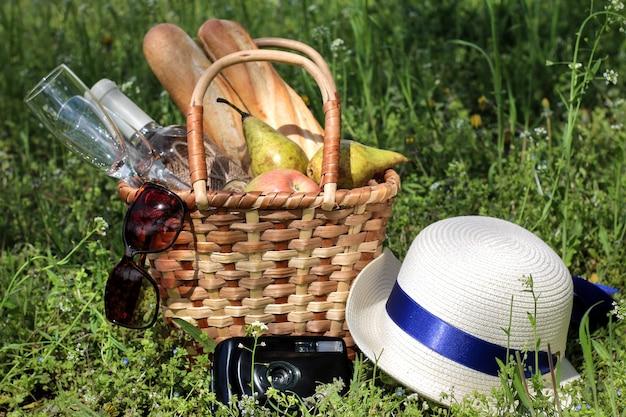 Cesta de vime para piquenique com produtos dentro e um chapéu, uma câmera e óculos de sol na grama verde.