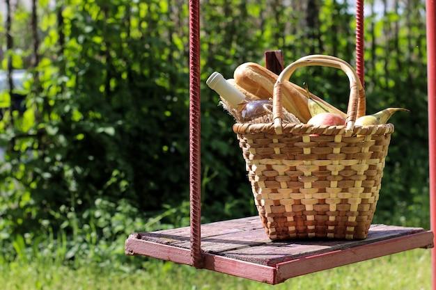 Cesta de vime para piquenique com vinho, frutas e outros produtos em um balanço com fundo de grama verde