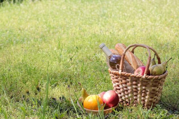 Cesta de vime piquenique com vinho, frutas e outros produtos na grama verde.