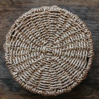 Cesta de vime redonda em um fundo de madeira. padrão de textura redonda. vista do topo. composição central.