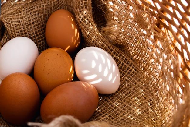Cesta de vime rústica com ovos marrons e brancos close-up