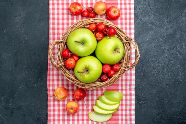 Cesta de vista de cima com frutas, maçãs verdes e cerejas doces na árvore de frescor de composição de frutas de baga cinza escuro