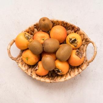 Cesta de vista superior com frutas exóticas em cima da mesa