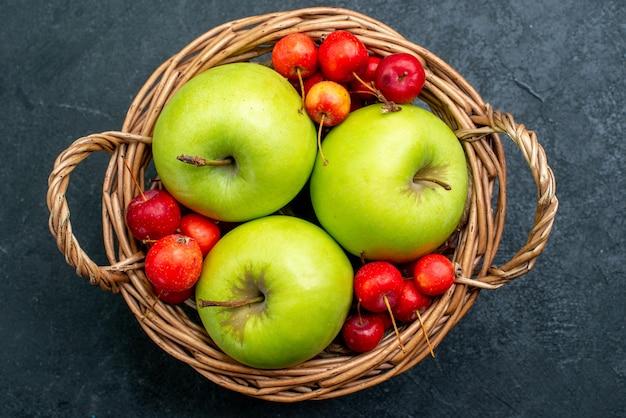 Cesta de vista superior com frutas, maçãs e cerejas doces na árvore de frescor da composição de frutas e frutas da mesa escura