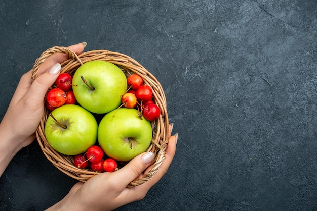 Cesta de vista superior com frutas, maçãs e cerejas doces na árvore de frescor de composição de frutas de frutas com superfície cinza-escuro