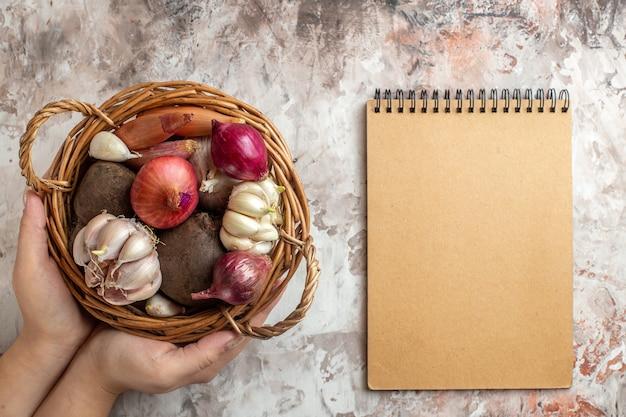 Cesta de vista superior com legumes, alho, cebola e beterraba com bloco de notas na cor clara de dieta de salada madura