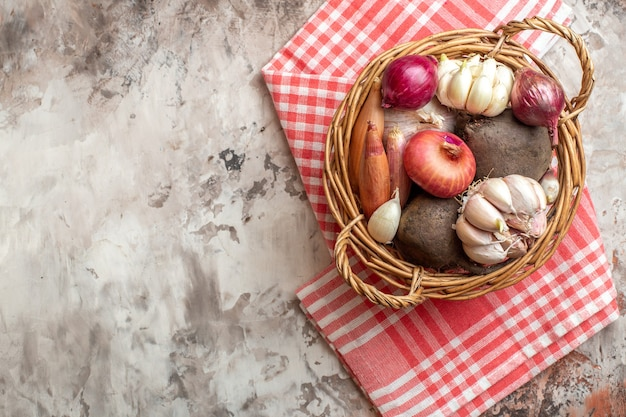Cesta de vista superior com legumes, alho, cebola e beterraba na foto clara, salada madura, dieta, cor, espaço livre para texto