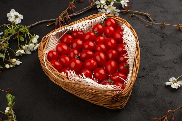 Cesta de vista superior com tomates frescos maduros no cinza