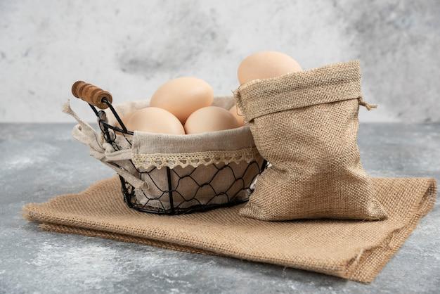 Cesta e saco de ovos crus frescos orgânicos na superfície de mármore.