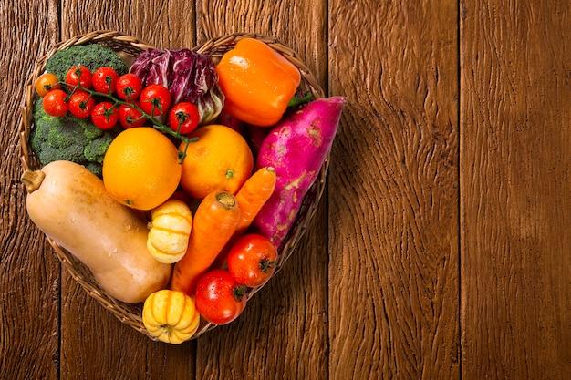 Cesta em forma de coração cheia de frutas e vegetais em um antigo fundo de madeira, vista superior, com espaço para texto.