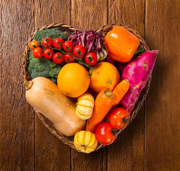 Cesta em forma de coração cheia de frutas e vegetais em um antigo fundo de madeira, vista superior,