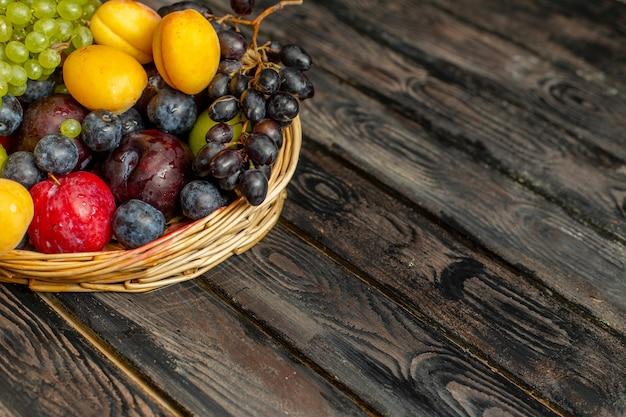 Cesta frontal com frutas maduras e azedas, como uvas, damascos, ameixas no fundo marrom rústico