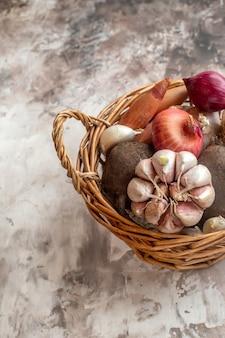 Cesta frontal com legumes, alho, cebola e beterraba em fundo claro