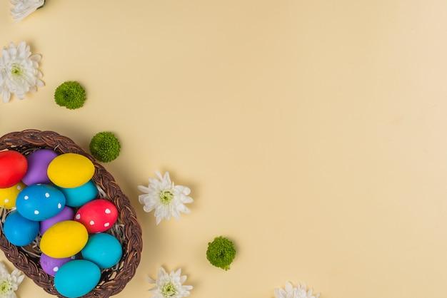 Cesta grande com ovos de páscoa coloridos na mesa