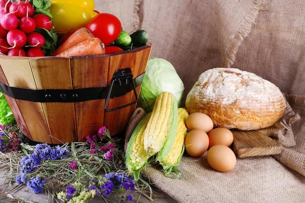 Cesta grande e redonda de madeira com legumes, leite e pão na superfície do saco