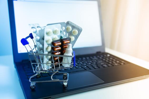 Cesta pequena com close-up de medicamentos. tela do laptop. conceito de compra online de medicamentos.