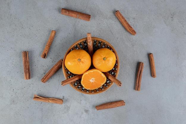 Cesta pequena de laranjas com cortes de canela na mesa de mármore.