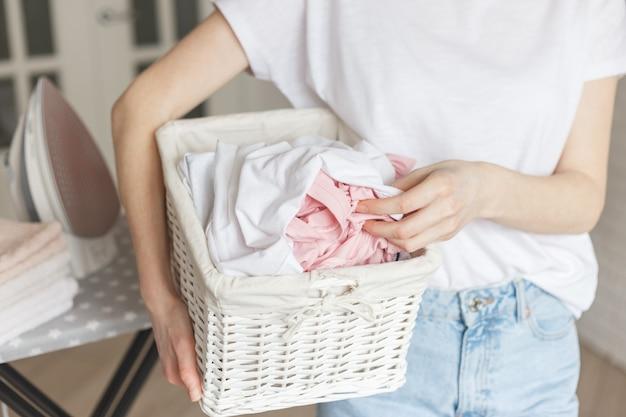 Cesta rústica de vime com roupa lavada a mão de mulher pronta a passar. close-up vista na cesta nas mãos. mulher na sala