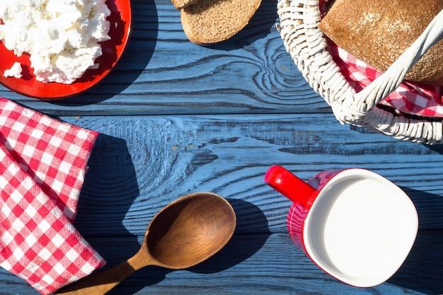 Cesta, um copo de leite, queijo cottage e pão em uma mesa de placas azuis. vista do topo