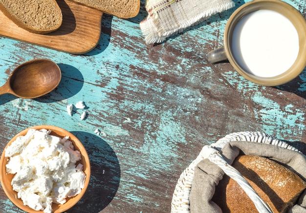 Cesta, um copo de leite, queijo cottage e pão em uma mesa de placas de azul claro. vista do topo