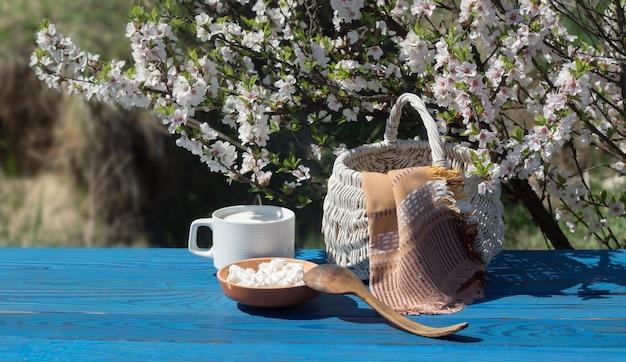 Cesta, uma xícara de leite e queijo cottage em uma mesa de placas azuis no fundo de um arbusto florido