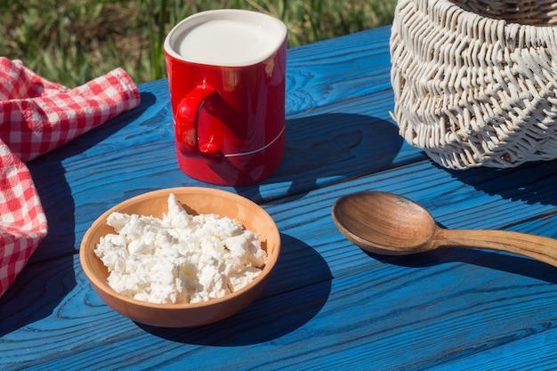 Cesta, uma xícara de leite e queijo cottage em uma mesa de placas azuis