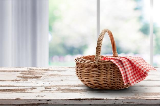 Cesta vazia com piquenique de guardanapo vermelho na maquete de lugar de mesa.