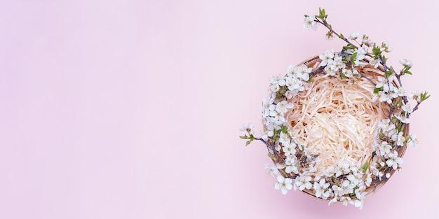 Cesta vazia com uma coroa de flores brancas em um fundo rosa. Foto Premium