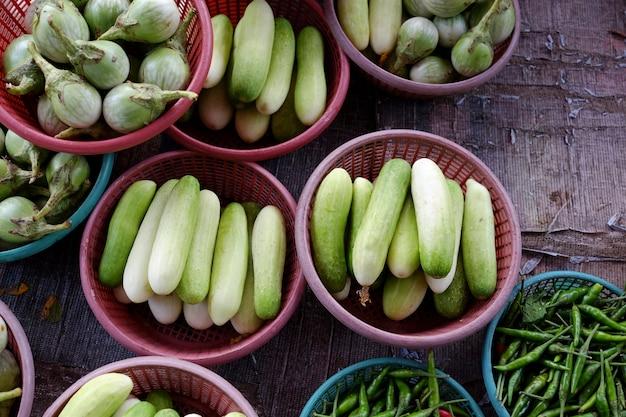 Cesta vegetal do mercado de tailândia que vende pepinos, pimentões e baga da barata.