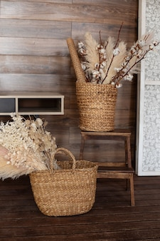 Cestas de vime com grama de pampa e flores secas no interior da sala de estar e decoração de outono