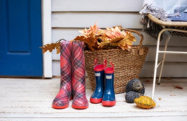 Cesto com folhas, abóbora e bota de borracha no quintal. botas de chuva xadrez e azuis da casa na varanda