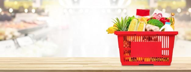 Cesto de compras cheio de comida e mantimentos na mesa no supermercado