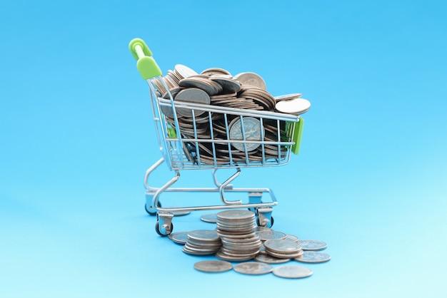 Cesto de compras com moedas. como lidar com o conceito de shopaholism