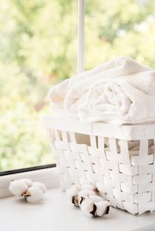 Cesto de roupa branca ao lado de uma janela