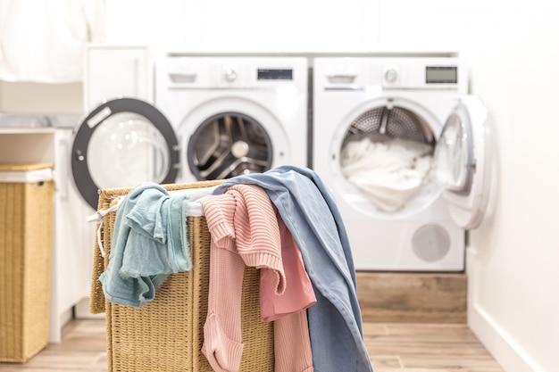 Cesto de roupa suja com roupas sujas com máquinas de lavar e secar ao fundo