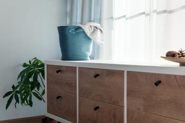 Cesto de roupa suja com toalha cinza. interior da elegante sala branca com cesto de roupa suja.