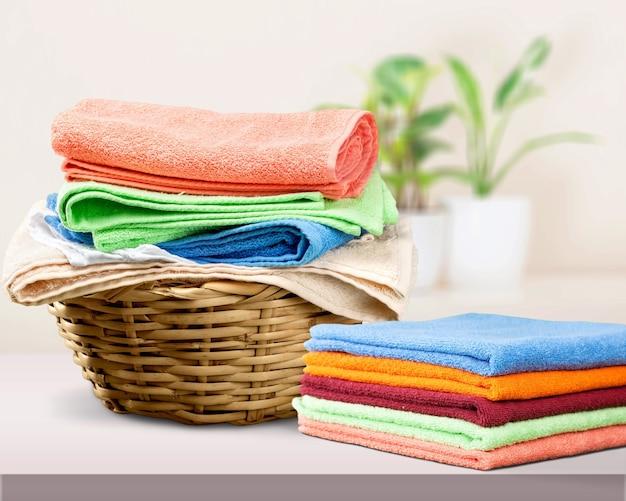 Cesto de roupa suja com toalhas coloridas no fundo