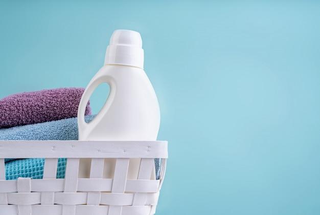 Cesto de roupa suja com uma garrafa de detergente e uma pilha de toalhas limpas na mesa branca isolada em fundo azul