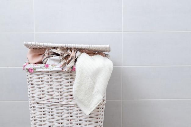 Cesto de roupa suja de vime branco na lavanderia. uma pilha de toalhas limpas.