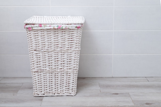 Cesto de roupa suja de vime branco na lavanderia.