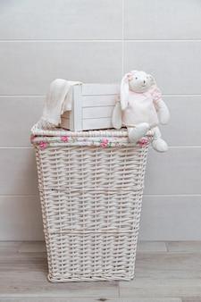 Cesto de roupa suja de vime em uma lavanderia. caixa de madeira branca e coelhinho de brinquedo branco em um vestido rosa