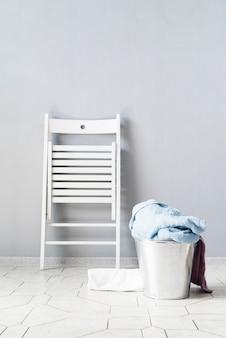 Cesto de roupa suja vista frontal com cadeira branca