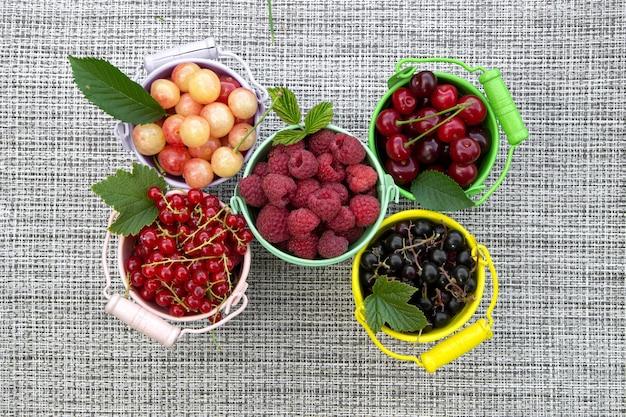 Cestos coloridos transbordando de frutas vermelhas misturadas no verão como framboesas, groselha e cereja