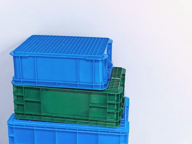 Cestos de plástico verdes e azuis empilhados contra uma parede branca
