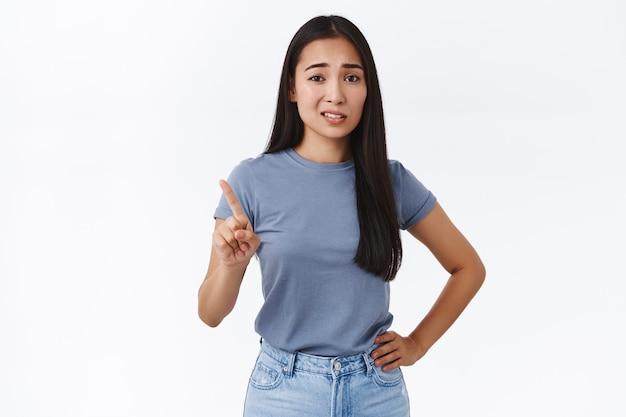 Cética e arrogante jovem asiática atrevida sacudindo o dedo em rejeição, recusando e olhando com desdém ou desprezo, subestimar alguém, ficar de pé na parede branca sem dar nenhuma chance