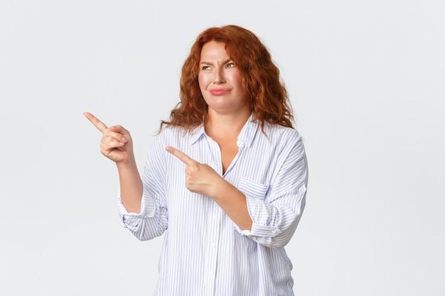Cética e decepcionada ruiva, mulher de meia-idade, mãe não gosta de banner promocional, apontando e olhando para o canto superior esquerdo e fazendo uma careta de julgamento, parede branca de pé.