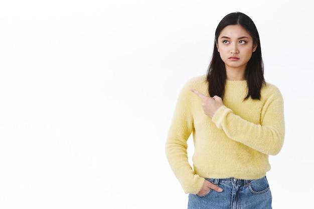 Cética e séria jovem linda asiática olhando, apontando para a esquerda para algo insatisfatório ou estranho, tendo dúvidas sobre a compra do produto no anúncio, parede branca em pé