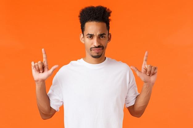 Cético, descontente e relutante, o jovem moderno hipster afro-americano não gosta de algo, franzindo a testa fazendo careta insatisfeito, apontando para cima discorda, julgando mau produto, parede laranja