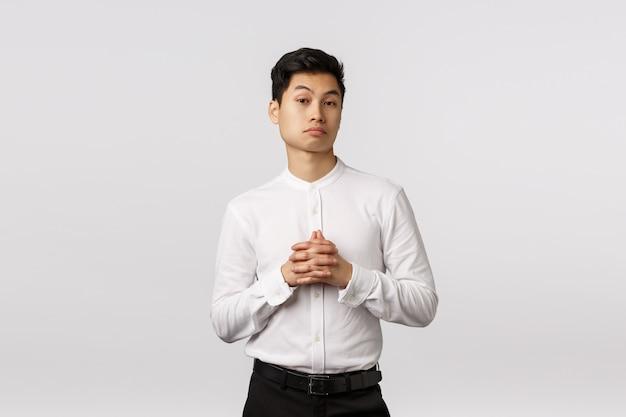 Cético e impressionado jovem empresário asiático considerar algo, cerrar as mãos juntas, levantando as sobrancelhas satisfeito, ouvir oferta interessante, ter reunião de negócios, em pé