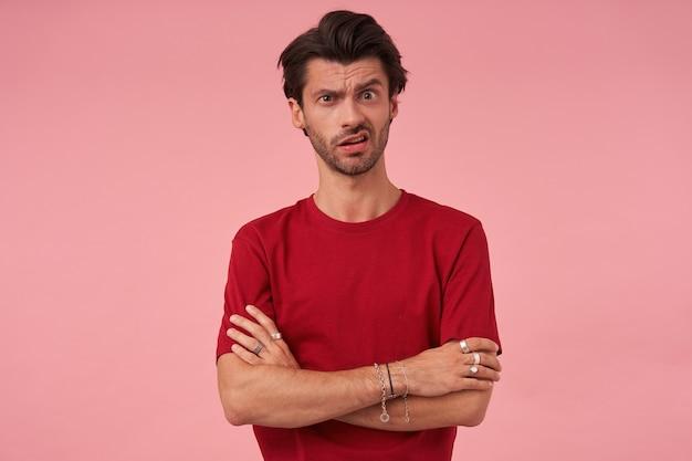 Cético e suspeito jovem com a barba por fazer e uma sobrancelha levantada questionando em uma camiseta vermelha pensando e em pé com os braços cruzados